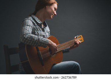 A young female musician plays the acoustic guitar before a plain dark background and under dramatic light.