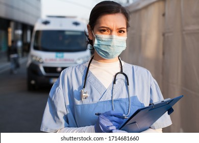 Young female NHS UK EMS doctor in front of healthcare ICU facility,wearing protective face mask holding medical patient health check form,Coronavirus COVID-19 pandemic outbreak crisis PPE shortage