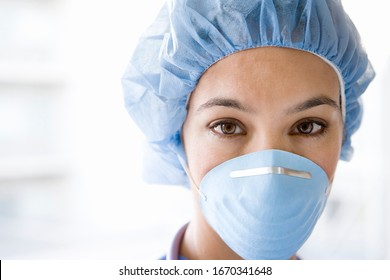 Young female nurse at camera wearing surgical mask and scrubs