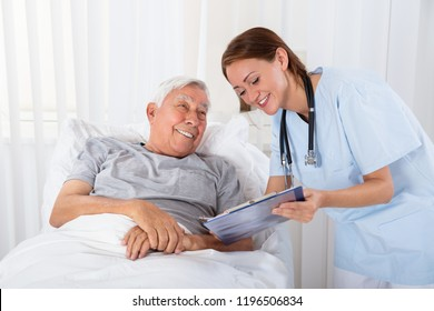 Young Female Nurse With Clipboard Visiting Senior Male Patient