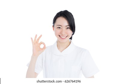 Young female nurse giving OK gesture, isolated on white background