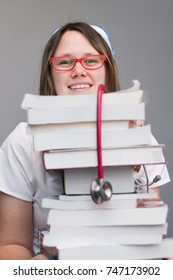 Young female nurse student portrait wearing white scrubs, cap holding tall stack of  nursing textbooks