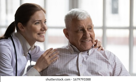 Young female nurse wearing white coat hugs old man grey-haired patient smiling look at distance. Concept of eldercare, health check-up, geriatrics medicine, social worker caretaker caring about senior