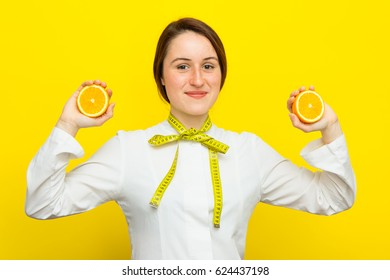 Young female nutritionist with half citrus in her hands on yellow background. Measure tape on her neck