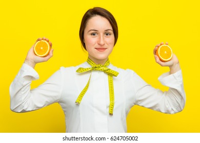 Young female nutritionist with half citrus in each hand on yellow background. Measure tape on her neck