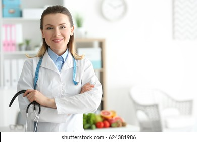 Young female nutritionist standing in her office
