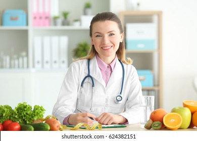 Young female nutritionist working in her office