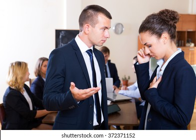 Young female office member getting notice of dismissal from chief at work