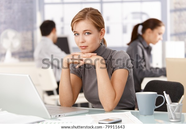 Young female office worker sitting at desk in office, using laptop, colleagues working in background.?