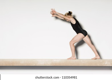 Young female on balance beam preparing to do handstand
