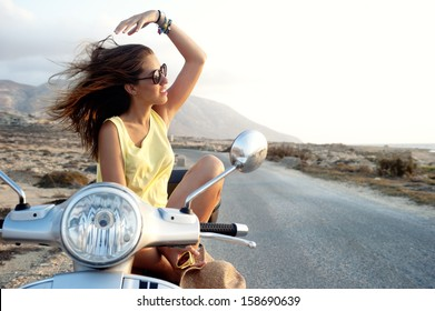 Young female on motorcycle trip. Young female enjoys a motorcycle trip and admires the view