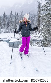 young female on nordic skiis standing in a snowy canadian winter scene