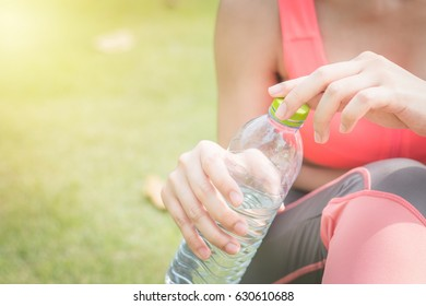 Young female open bottled water after fitness training at the park.