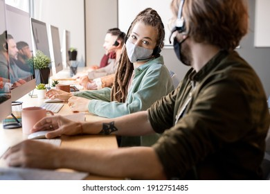Young female operator of call center in protective mask looking at one of colleagues while consulting with him about client question