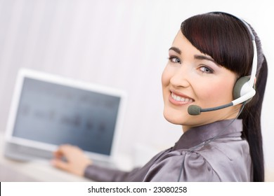 Young female operator wearing a headset works on her laptop, looking at camera.