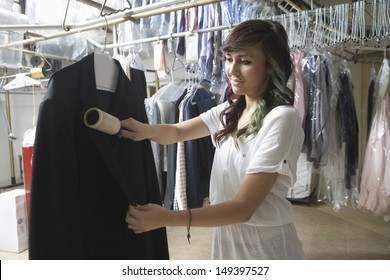 Young female owner cleaning coat with brush in laundry