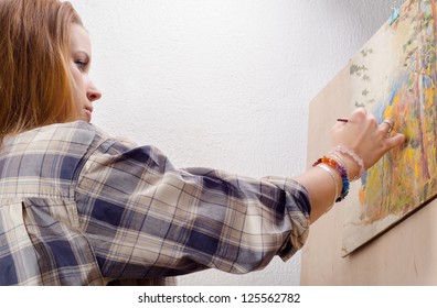 Young female painter painting landscape in her art studio.