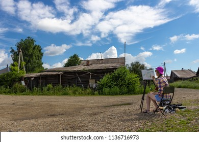 Young female painter sitting at his easel in the open air.