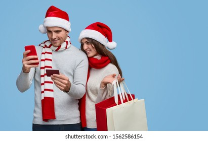 Young female with paper bags smiling and watching boyfriend entering credit card credentials into smartphone while making Christmas purchases online against blue background