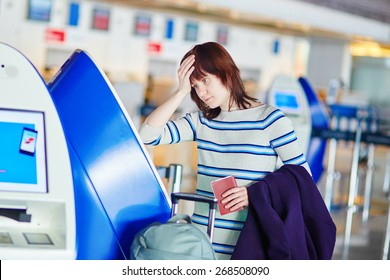 Young female passenger at the airport, doing self check-in, stressed and concerned. Missed, delayed or cancelled flight concept