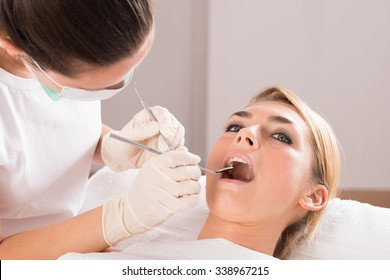 Young female patient getting dental checkup at clinic
