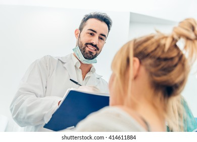 Young female patient looking at dentist while he making notes