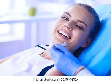 Young Female patient with open mouth examining dental inspection at dentist office.