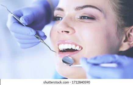 Paciente joven con boca abierta que examina la inspección dental en la oficina del dentista.
