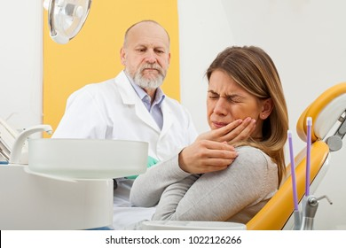 Young female patient with severe toothache at the dentist office with elderly male dentist in the background