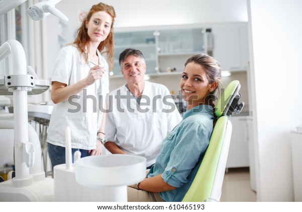 Young  female patient sitting on dental chair and preparing for treatment.