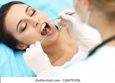 Young female patient visiting dentist office.Beautiful woman with healthy straight white teeth sitting at dental chair with open mouth during oral checkup while doctor working at teeth