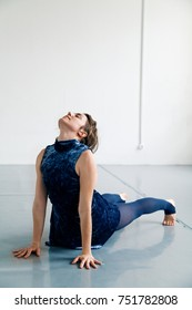 Young female performer stretching in white spacious loft. Natural lighting. Vertical composition, copy space.