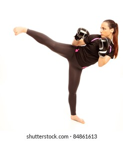 A young female performing a martial arts kick on an isolated white background