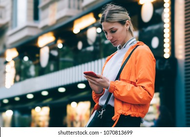 Young female person in bright orange jacket with modern mobile phone device while standing outdoors on city bokeh lights background.Woman typing text message on smartphone using 4G internet connection
