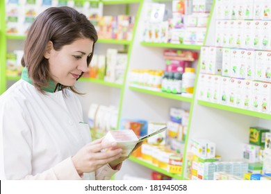 Young female pharmacist in a drugstore working on a tablet pc