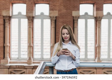 Young female with the phone near the handrail. Horizontal indoors shot.