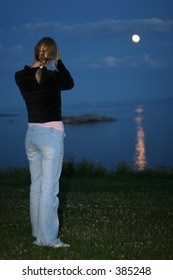 young female photographer captures rising moon reflected on water