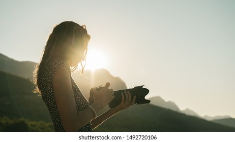 Young female photographer looking at her dslr camera adjusting the properties as she stands in beautiful nature lit by the light of rising sun.