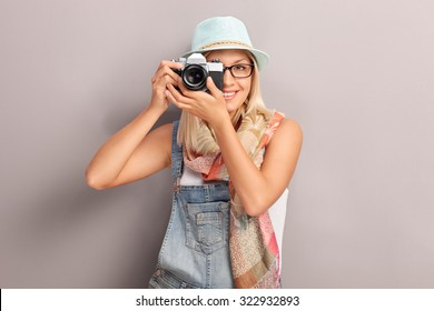 Young female photographer photographing with a retro camera and smiling