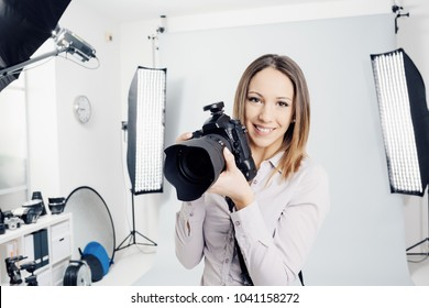 Young female photographer posing in the photo studio, she is smiling and holding a professional digital camera