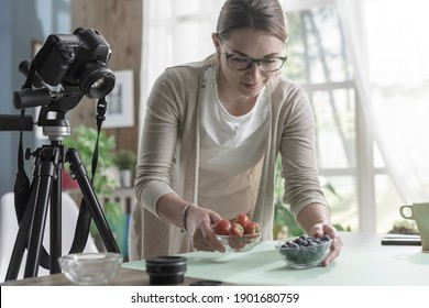 Young female photographer preparing food for a shooting, she is working from home