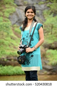 Young female photographer with professional digital camera in natural landscape on background.