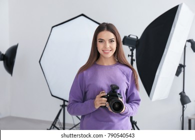 Young female photographer in professional studio