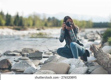 Young female photographer shooting, natural landscape on background
