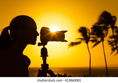 Young female photographer shooting the sunset.