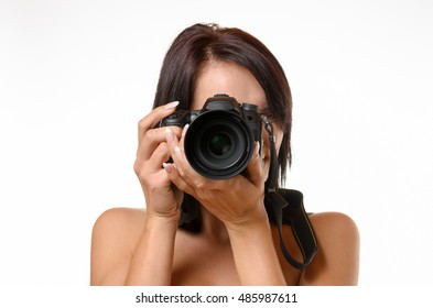 Young female photographer taking a photograph aiming the lens at the viewer, head and shoulders isolated on white