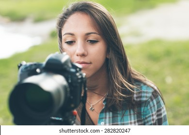 Young female photographer and videomaker shooting in a green natural setting with grass on background