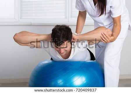 Young Female Physiotherapist Assisting Man While Doing Exercise On Fitness Ball