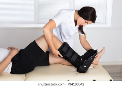 Young Female Physiotherapist Fixing Walking Brace On Patient's Leg In Hospital