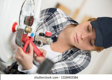 young female plumber working on boiler with adjustable wrench